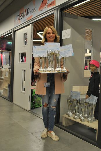 Secretary of Organising Committee Jelizaveta Birjukova with trophys front of Icestar shop